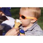 Baby wearing Baby Banz Adventure Banz Orange sunglasses earing ice cream