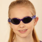 Baby Banz Adventure Banz sunglasses in Purple Tortoiseshell on a five year old