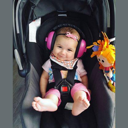 Baby in stroller wearing Mini Muffs in Magenta