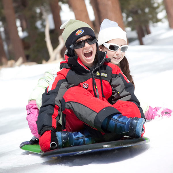 Boy and girl tobogganing wearing JBanz sunglasses