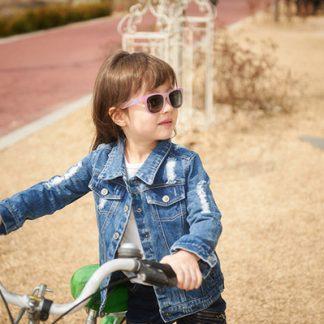 Girl riding bike wearing JBanz Chameleon sunglasses
