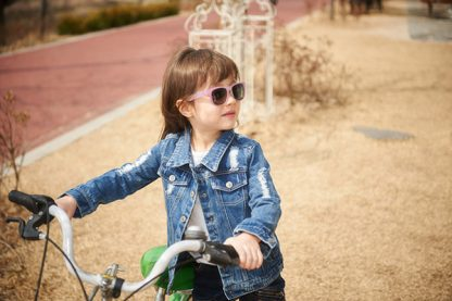 Girl riding bike wearing JBanz Chameleon sunglasses