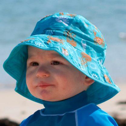 Boy on beach in Reversible Tidal Aqua sunhat