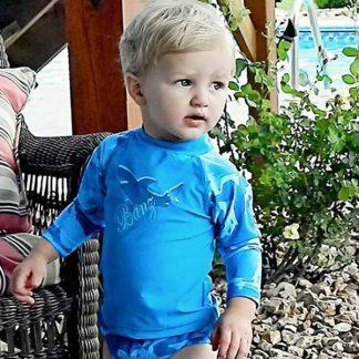 Boy in a long-sleeved Fin Frenzy Blue rash shirt