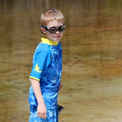 Boy in short-sleeved Fin Frenzy Pattern rash shirt by the water