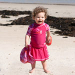 Toddler in a short-sleeved Pink Graffiti rash shirt and swim skirt