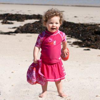 Toddler in a short-sleeved Pink Graffiti rash shirt and swim skirt