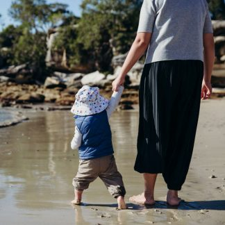 Boy wearing Seaside bucket sunhat at the beach