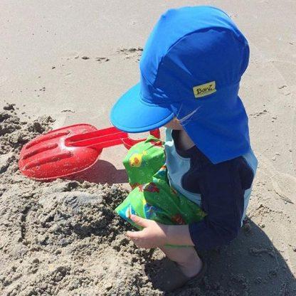 Boy in Flap Hat in True Blue at the beach