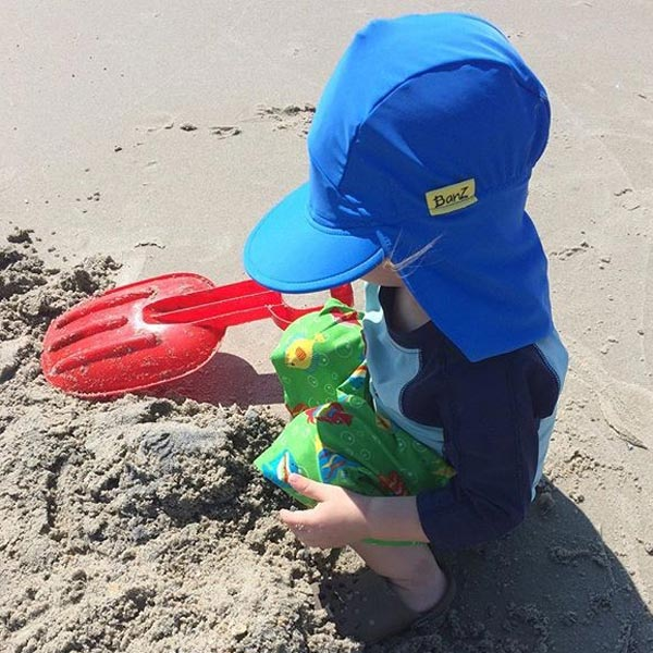 Boy in Flap Hat in True Blue at the beach