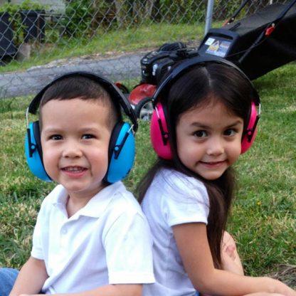 Boy and girl in earmuffs beside lawnmower