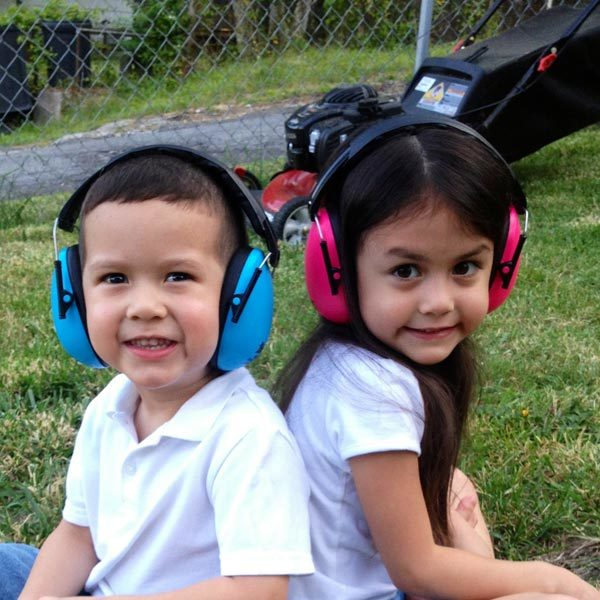 Boy and girl in earmuffs beside lawnmower