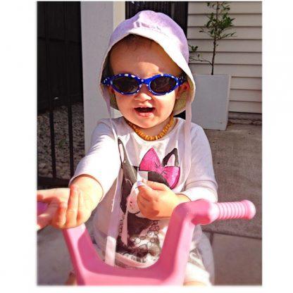 little girl on trike in Adventure Blue Dot sunglasses